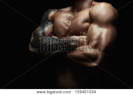 Athletic man's torso. Unrecognizable male fitness model show naked muscular body. Strong hands, chest and shoulder muscles and biceps. Studio shot on black background, low key. Bodybuilding concept