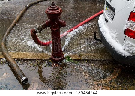 Uzhgorod Ukraine - December 1 2016: Water flowing under the worthless old fire hydrant during extinguishing a fire on a city street.