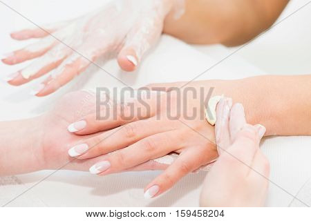 Hand cream application at beauty spa, toned image, white