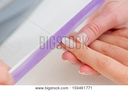 Manicuring hands - using nail file, white