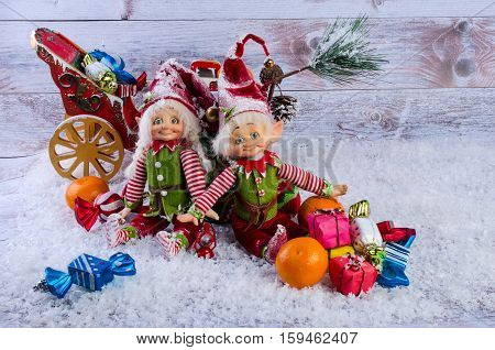 Christmas scene with elves Christmas socks tangerines and gifts. On a light background.