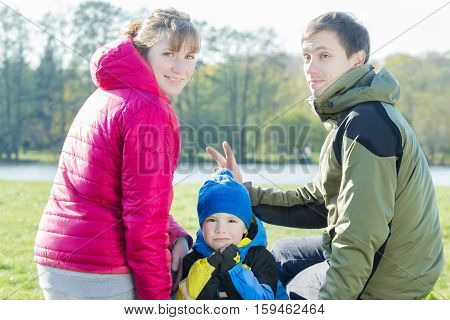 Funny family portrait of parents putting bunny ears to their son