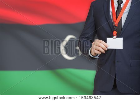 Businessman Holding Name Card Badge On A Lanyard With A National Flag On Background - Libya