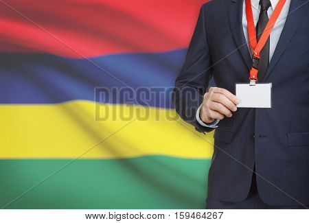 Businessman Holding Name Card Badge On A Lanyard With A National Flag On Background - Mauritius