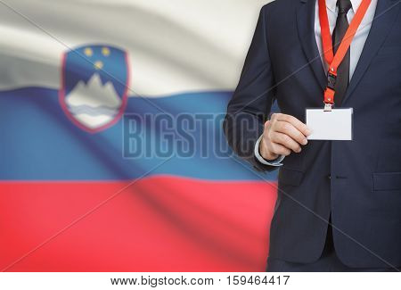 Businessman Holding Name Card Badge On A Lanyard With A National Flag On Background - Slovenia