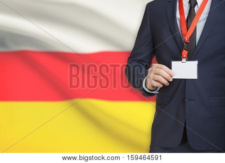 Businessman Holding Name Card Badge On A Lanyard With A National Flag On Background - South Ossetia