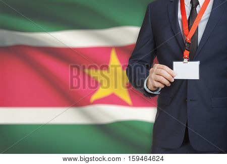 Businessman Holding Name Card Badge On A Lanyard With A National Flag On Background - Suriname