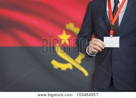Businessman Holding Name Card Badge On A Lanyard With A National Flag On Background - Angola