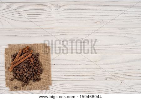 Coffee beans with cinnamon and star anise on an old wooden table. Top view.