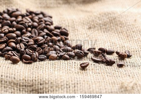 Brown roasted coffee beans on sackcloth, close up