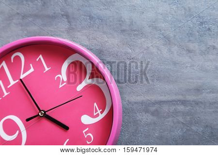 Pink Round Clock On A Grey Wooden Table