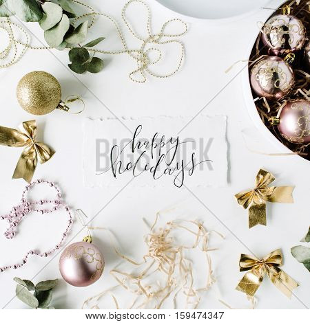 calligraphy words happy holidays and frame made of christmas decoration with christmas balls tinsel bow eucalyptus. christmas wallpaper. flat lay top view