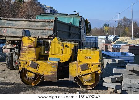 Truck and small yellow roller on the construction site