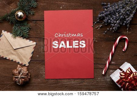 Christmas sale and price reduction. Red sheet, gift box, candy, lavender, pine, ball, envelope and gingerbread on wooden table.