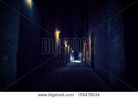 Dark and narrow urban city alley at night