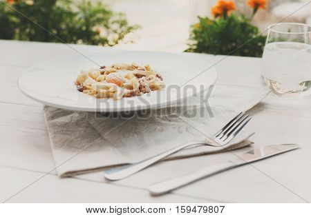 Traditional italian carbonara pasta with bacon, egg yolk and parmesan decorated with basil on white round plate in outdoors summer restaurant interior. Candid image, filtered
