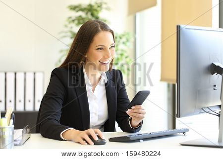 Happy businesswoman working checking smart phone information with a desktop computer at office