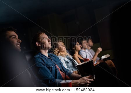 Young man with friends in cinema hall watching movie. Group of people watching movie in theater.