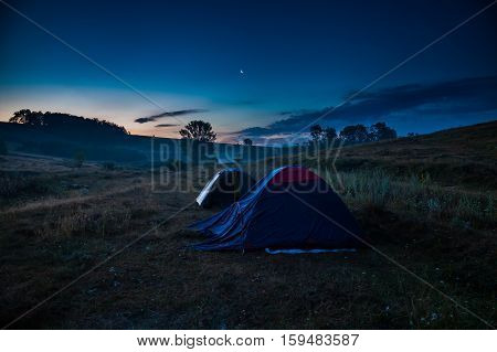 Tourist camp with tents at sunrise with the moon in the sky