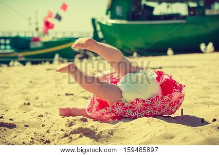 A little baby with diaper lying upside down on beach