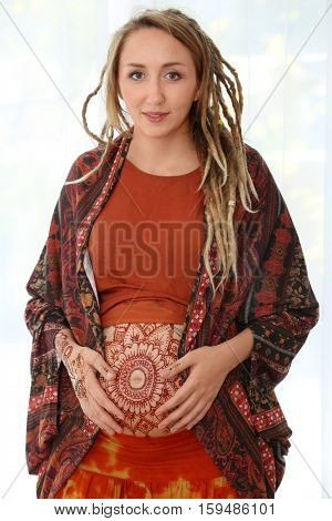 Young pregnant woman with henna tattoo on belly on light background