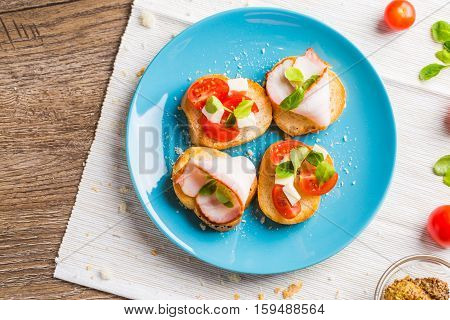 Traditional Italian antipasti bruschetta with tomato, cheese and bacon. Flat lay.
