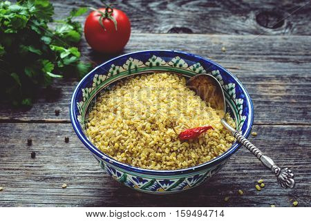 Raw bulgur wheat grains in colorful arabic bowl, fresh parsley, tomato and peppers for cooking. Wooden table background, horizontal composition, toned