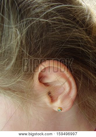 Ear of the child with an ear ring in ears