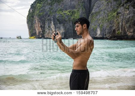 Half body shot of a handsome young man using cell phone to take photo, standing on a beach in Phuket Island, Thailand, shirtless wearing boxer shorts, showing muscular fit body