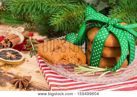 Cookies Tied With Green Ribbon And Christmas Decoration, On Wooden Surface.