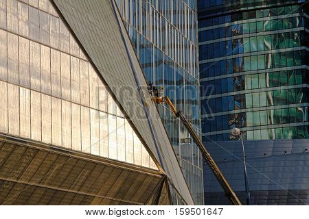 Moscow Russia - October 21 2015: Construction worker working at height on modern commercial skyscraper in a gondola in Moscow