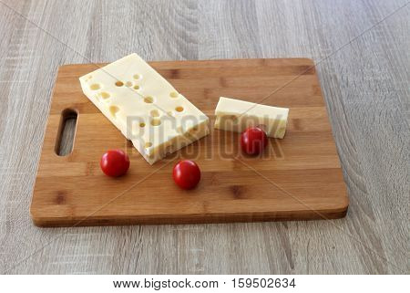 two pieces of cheese Cheese with tomatoes on a cutting board