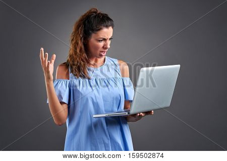 A beautiful young woman standing and felling worried while looking at a laptop in her hand.