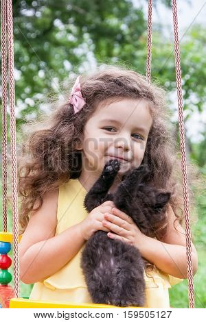 Baby girl holding a black kitten sitting on a swing outdoors