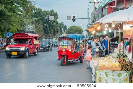 CHIANG MAI, THAILAND - FEBRUARY 6, 2016: Iconic traditional red truck taxi and tuk tuk roaming the streets of Chiang Mai. Chiang Mai is a major tourist destination in northern Thailand.