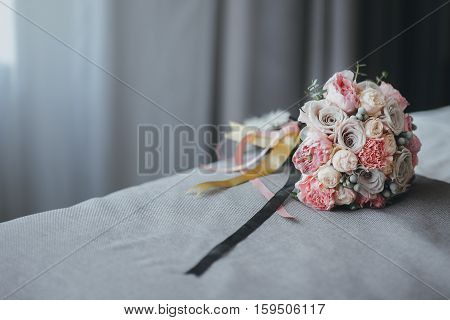 pink bridal bouquet with ribbons on the bed