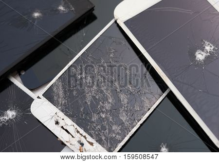 several broken smart phone screens on a white background
