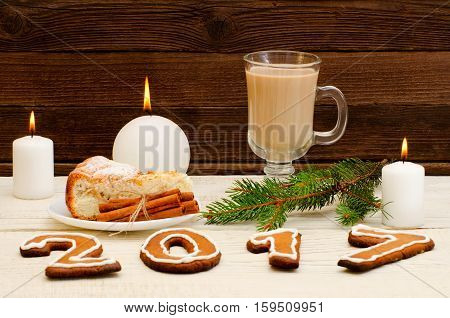 Christmas dinner the figure in 2017 of gingerbread spruce branch candle cappuccino and apple pie on a wooden table