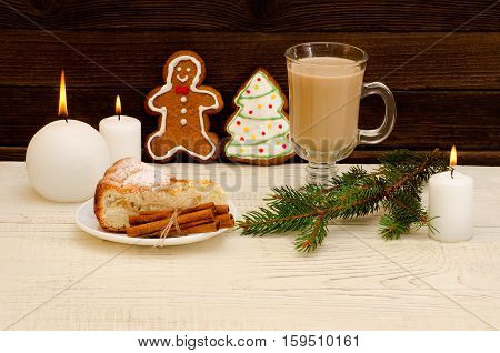 Christmas installation. Fir branch gingerbread pots cake and candles on wooden background
