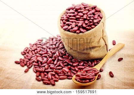 red beans in spoon and pile of red beans on sack cloth