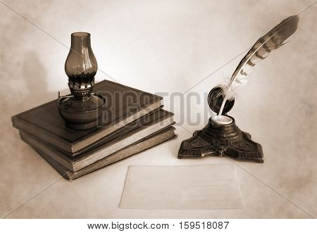 Blank paper card oil lamp and inkwell with a quill pen as a concept of greetings on holidays. Photo in sepia tone.