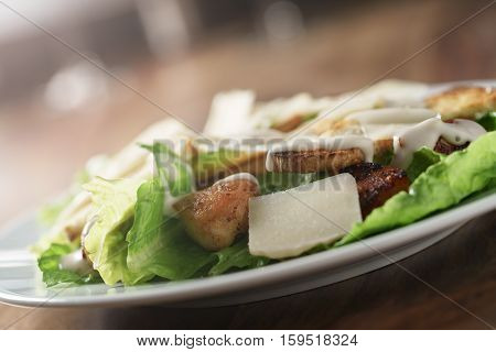 angle shot of caesar salad with chicken on old wooden table, shallow focus