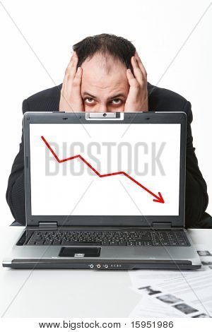 Photo of middle aged employer hiding behind laptop with falling graph on its screen