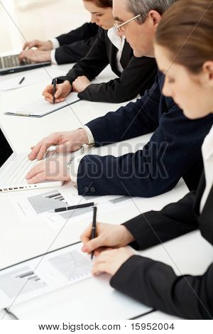 Image of row of people writing on papers and typing at briefing