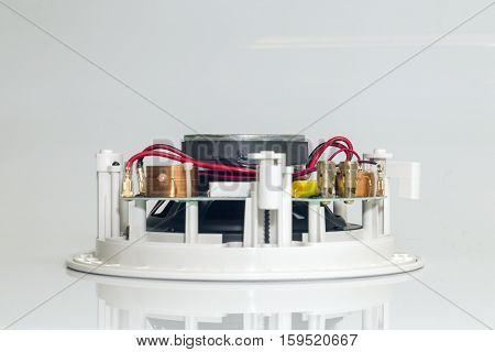 Red wires and golden clips on a white loudspeaker close view
