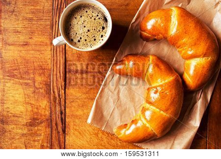 Breakfast with croissants and cup of espresso coffee over wooden table