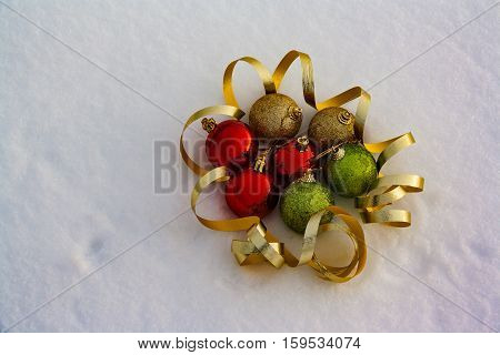 Red golden and green Christmas balls on snow background