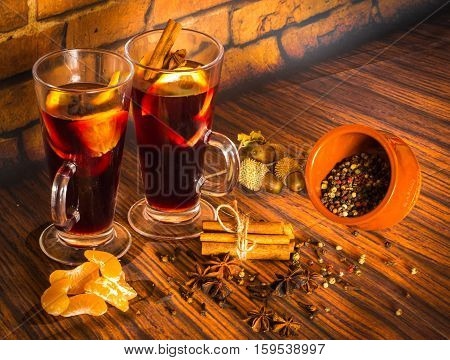 Image of christmas hot mulled wine with cinnamon cardamom anise and oranges on on wooden background