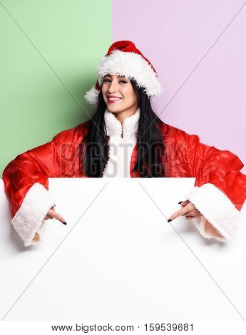 pretty cute sexy santa girl or smiling brunette woman in red sweater showing with christmas or xmas hat on purple green studio background copy space