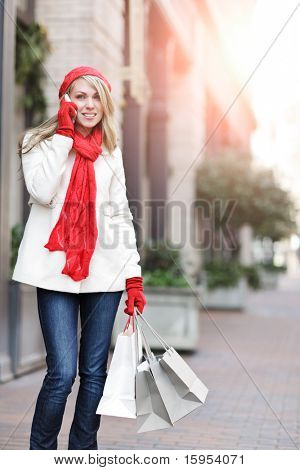 A shopping caucasian woman carrying shopping bags and talking on the phone at an outdoor shopping mall